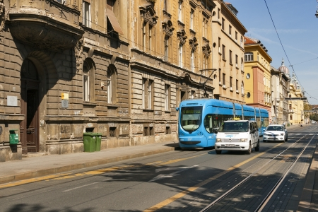 ZAGREB, CROATIA - AUGUST 21: People travel along city street with old houses by tram and taxi in Zagreb, Croatia on August 21, 2012. Zagreb Tram run by the Zagrebacki elektricni tramvaj (ZET).