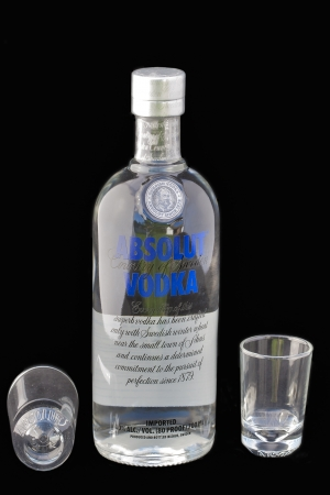 Bottle of Absolut vodka and empty shot glass against black background