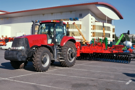 plough machine: Closeup of modern red tractor for plough up on parking lot
