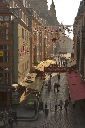 DRESDEN, GERMANY - NOVEMBER 14: People walk along city narrow Munzgasse street with small cafes, restaurants and beer gardens decorated for Christmas on November 14, 2012 in Dresden, Germany.Munzgasse street is the largest mile of restaurants but also a t