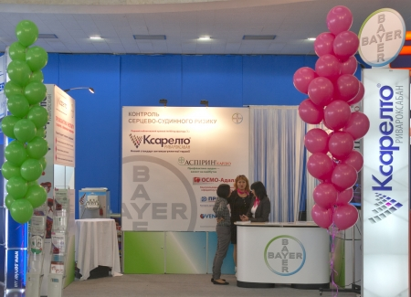 pharm: KIEV, UKRAINE - September 27: Presenters work on booth of Bayer AG German chemical and pharmaceutical company during XIII National Congress of Cardiology on September 27, 2012 in Kiev, Ukraine.