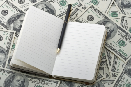 notebook with black pen on American 100 USD banknotes backgound. Space for copy inside. photo