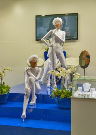 Kiev, Ukraine - May 16, 2012: Presenters in white closes work on Zarina Jewelry House booth during Spring Jeweler Expo exhibition at KyivExpoPlaza Exhibition Center in Kiev, Ukraine.