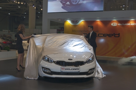 to proceed: KIEV, UKRAINE - MAY 29: Presenters remove the sheet from new Korean car model KIA Pro_Ceed on display of SIA 2013 Kyiv International Motor Show in International Exhibition Centre on May 29, 2013 in Kiev, Ukraine.