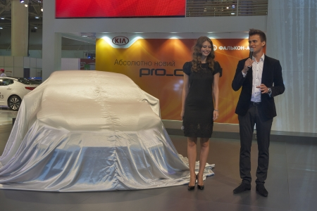 to proceed: KIEV, UKRAINE - MAY 29: Presenters present new Korean car model KIA Pro_Ceed covered be sheet on display of SIA 2013 Kyiv International Motor Show in International Exhibition Centre on May 29, 2013 in Kiev, Ukraine.