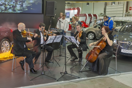 KIEV, UKRAINE - MAY 29: Quartet of musicians play classical music at presentation of new German car model Opel Cascada on display of SIA 2013 The 21st Kyiv International Motor Show in International Exhibition Centre on May 29, 2013 in Kiev, Ukraine. Editorial