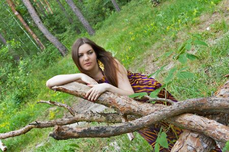 Sad young pretty woman lying on pine logs in the forest photo