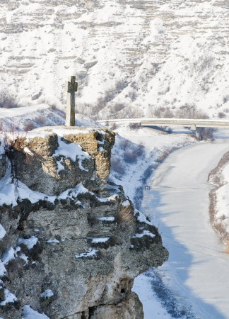 Winter stone cross on the mountain. Orhei Vechi, Moldova. photo