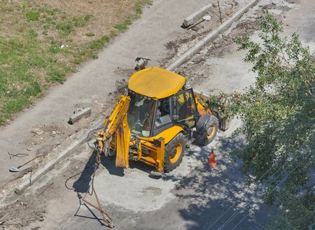small tractor performs road works to repair pavement edge. upper view photo