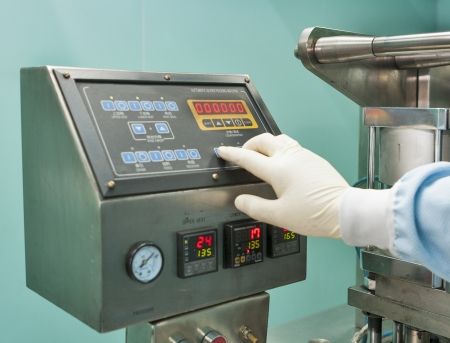 bliser packing machine remote control and human hand in gloves 免版税图像