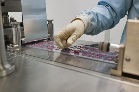 pharmaceutical production with bliser packing machine and human hand in gloves