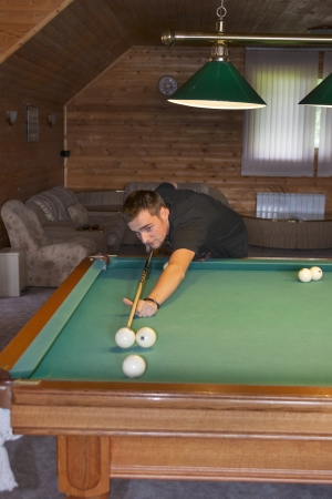 young man playing billiards in the billiard room photo