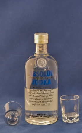 KIEV, UKRAINE - APRIL 30, 2012  Bottle of Absolut vodka blue label and empty shot glasses against blue  Absolut is a brand of vodka produced in Sweden and owned by group Pernod Ricard since 2008
