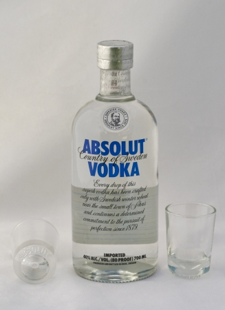 KIEV, UKRAINE - APRIL 30, 2012: Bottle of Absolut vodka blue label and empty shot glasses against white. Absolut is a brand of vodka produced in Sweden and owned by group Pernod Ricard since 2008.