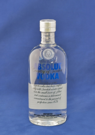 KIEV, UKRAINE - APRIL 30, 2012: Bottle of Absolut vodka blue label against blue background. Absolut is a brand of vodka produced in Sweden and owned by group Pernod Ricard since 2008.