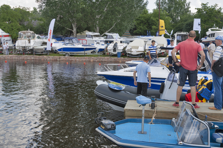 KIEV, UKRAINE - JUNE 06, 2013  Visitors visit motor boats moored on display of IBYS International Boat and Yacht Show in Chervona Kalyna yacht-club  All the latest technologies and samples of produced equipment for sailing are shown there  Editorial