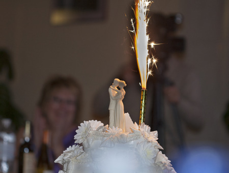 people celebrating wedding with cake and candle closeup photo
