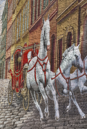 KIEV, UKRAINE - FEBRUARY 18, 2014: Unknown artist street graffiti on building brick wall with red coach and three white horses rushing on the street.