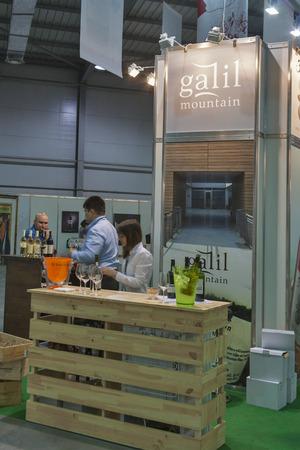 wino: People tasting wine at Galil Mountain booth during the Ukrainian festival Polyana Wino Fest 2013 in in Kiev, Ukraine. Galil Mountain is a Israelil premium wine brand.
