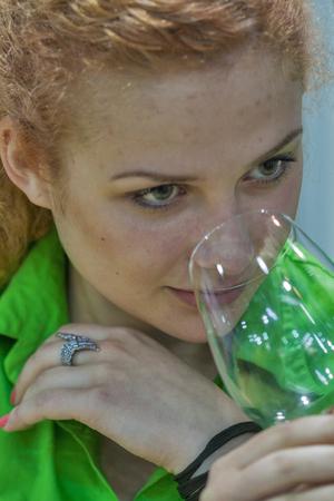 wino: Unrecognized woman sommelier tasting wine during the Ukrainian festival Polyana Wino Fest 2013 in in Kiev, Ukraine.