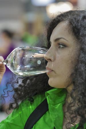 wino: Unrecognized young woman sommelier tasting white wine during the Ukrainian festival Polyana Wino Fest 2013 in in Kiev, Ukraine.