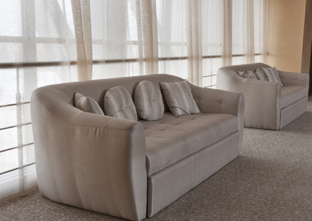 interior with beige sofa by the window photo