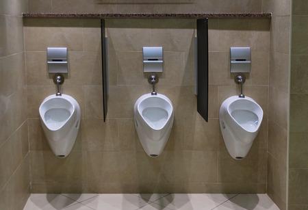 타일 바닥과 벽을 가진 현대 남성 화장실 시설의 소변 세트 스톡 콘텐츠