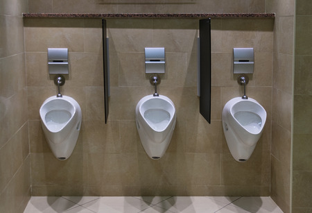Set of urinals in a modern male toilet facility, with tiled floor and wall photo