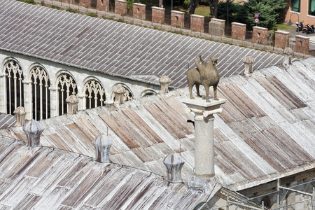 camposanto: Pisa Camposanto cemetery roof with fantastic creature statue. Cemetery was constructed in 1278 to house the sacred dirt brought back from Golgotha during the Crusades. It then became the burial place of the Pisan upper class. Editorial