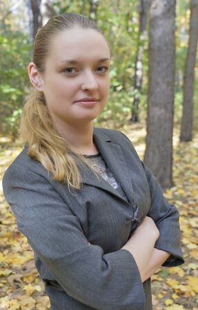pretty young woman in a gray business dress standing in the autumn forest half-turned with arms crossed photo