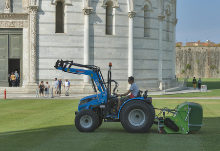 mows: PISA, ITALY - SEPTEMBER 04, 2014: Unrecognizable worker mows the grass on a tractor in front of the Baptistry, which is visited by tourists in the Square of Miracles. This site is the main tourist attraction in Pisa.