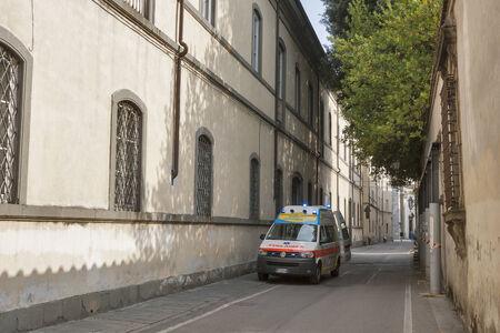 flashers: Lucca, Italia - 06 de septiembre 2014: Irreconocible personas caminan por la calle con el coche de la ambulancia en un hogar de ancianos en Lucca, Italia.