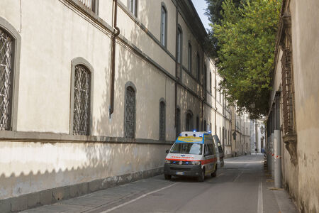 flashers: LUCCA, ITALY - SEPTEMBER 06, 2014: Unrecognizable people walk along the street with ambulance car in nursing home in Lucca, Italy.