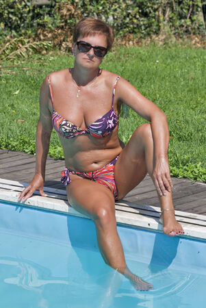 attractive tanned caucasian middle aged woman with short hair in a varicolored bikini and sunglasses sitting on the edge of swimming outdoor pool