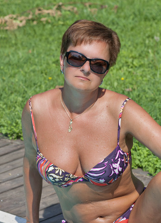 attractive tanned caucasian middle aged woman with short hair in a varicolored bikini and sunglasses sitting after swimming in outdoor pool