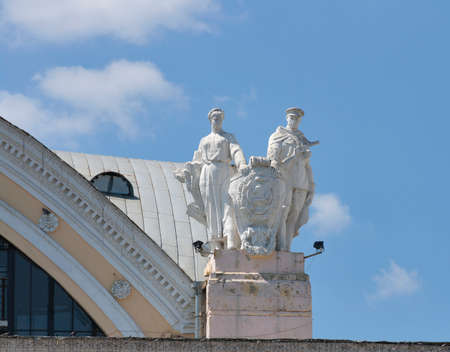 emblem of ukraine: The old Soviet statue of woman collective farmer and soldier with the emblem of the Soviet Union on the roof of the passenger train station in Kharkiv, Ukraine Stock Photo
