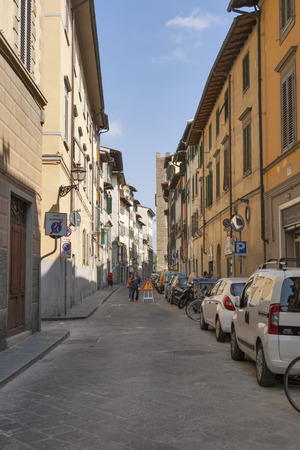 FLORENCE, ITALY - SEPTEMBER 09, 2014: Unrecognized pedestrians walk along city narrow street with parked cars and motorbikes. Florence is the administrative center of the region of Tuscany. Population of more than 373,000 people.