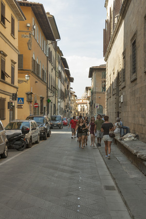 unrecognized: FLORENCE, ITALY - SEPTEMBER 09, 2014: Unrecognized pedestrians walk along city narrow street with parked cars and motorbikes. Florence is the administrative center of the region of Tuscany. Population of more than 373,000 people.