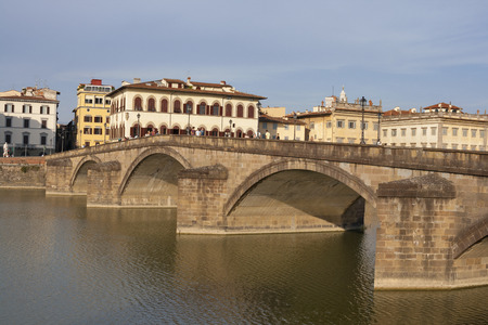 mention: FLORENCE, ITALY - SEPTEMBER 09, 2014: Unrecognizable people walk along Alla Carraia bridge over Arno River. The first mention of the bridge built in wood dates back to 1218. The current structure designed by Fagiuoli, completed in 1948.