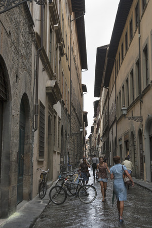 FLORENCE, ITALY - SEPTEMBER 10, 2014: Unrecognized pedestrians walk along city narrow street with parked bicycles. Florence is the administrative center of the region of Tuscany. Population of more than 373,000 people.