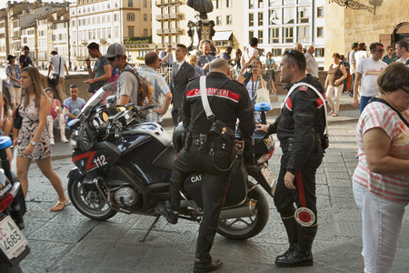 populations: FLORENCE, ITALY - SEPTEMBER 09, 2014: Carabinieri work among the people crowd on Ponte Vecchio. It is the national military police of Italy policing both military and civilian populations. Since 2001 it is one of the four Italian Armed Forces.