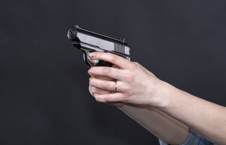 Caucasian women outstretched arms holding a black gun, fingers on the trigger. Against black background. photo