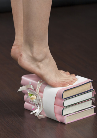 Caucasian young female feet standing on tiptoe on stack of books in pink covers closeup