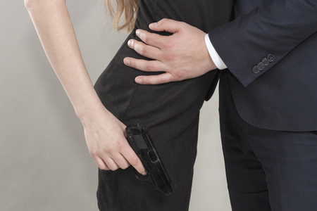 Caucasian man in a black suit hugging a blonde woman in a black dress, a woman holding a black gun in her right hand Stock Photo