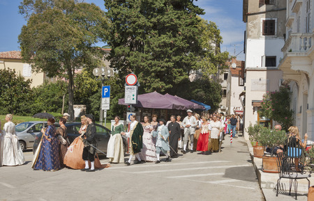 evoke: POREC, CROATIA - SEPTEMBER 14, 2014: Unrecognizable people dressed in medieval clothes walk along the streets of the city during 8th Historical Festival Giostra and evoke for the spectators life in the Baroque period.