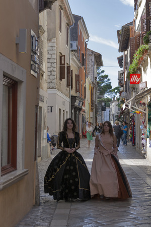 evoke: POREC, CROATIA - SEPTEMBER 14, 2014: Unrecognizable girls dressed in medieval clothes on the streets of the city during 8th Historical Festival Giostra and evoke for the spectators life in the Baroque period. Editorial