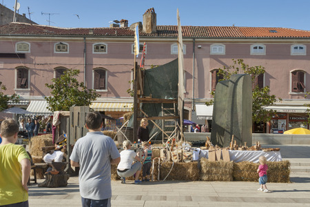 historical events: POREC, CROATIA - SEPTEMBER 14, 2014: Unrecognizable people visit street market at 8th Historical Festival Giostra. Festival stems from historical facts, so its events are connected to 18th century.
