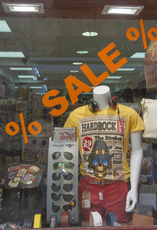 intent: POREC, CROATIA - SEPTEMBER 14, 2014: Sale showcase of unknown youth clothes store with exposed Hard Rock t-shirt, Pilot sunglasses, unknown belts and bags. Window shopping is a browsing of goods by a consumer with no intent to purchase, either as a recrea