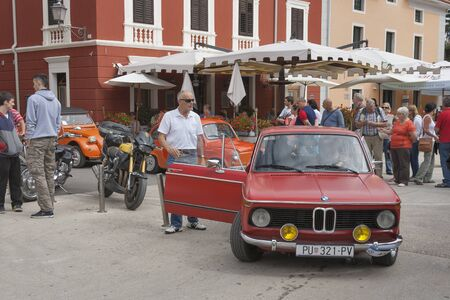 old timer: NOVIGRAD, CROATIA - SEPTEMBER 13, 2014: Unrecognizable people watch the parade of vintage cars on the streets on 5th International Old Timer Car Rally. The event organized by the old timer club Eppur si muove from Umag. Editorial