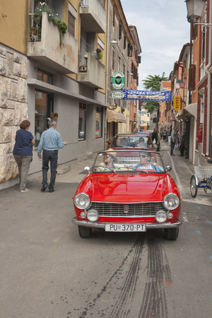 old timer: NOVIGRAD, CROATIA - SEPTEMBER 13, 2014: Unrecognizable people watch the parade of vintage cars on the narrow streets on 5th International Old Timer Car Rally. The event organized by the old timer club Eppur si muove from Umag.